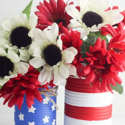 Two vases made of tin cans and painted to look like the American Flag.