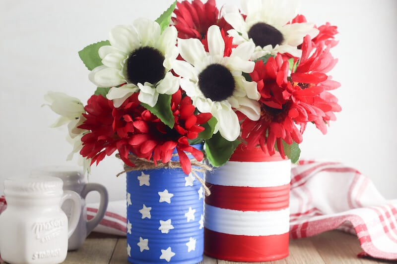 American flag vases on a table and filled with red and white flowers.