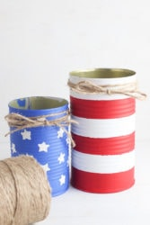 Two tin cans painted to look like the american flag with twine wrapped around the top of them.