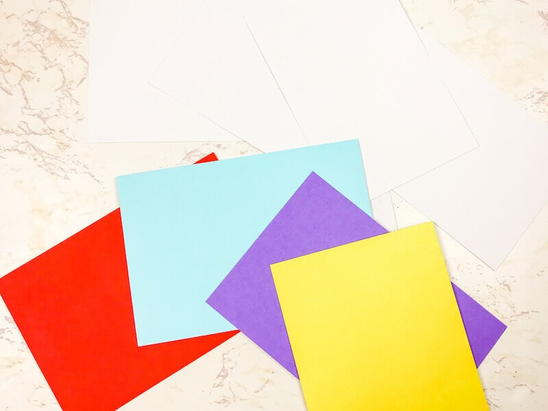 White note cards fanned out above colored envelopes.