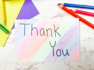 A rainbow colored card with the words Thank You next to a pile of colored pencils.