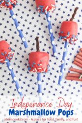 "Five marshmallow pops decorated to look like firecrackers with the words ""Independence Day Marshmallow Pops"" in red and blue lettering."