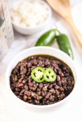 A white bowl of cuban black beans next to an instant pot and two jalapeños.