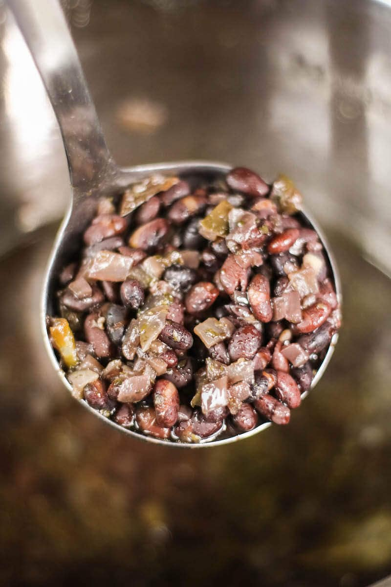 A ladle full of cuban black beans over the inside of the inside of the instant pot with cooked beans inside.