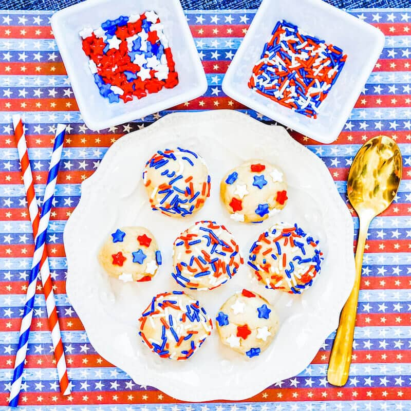 A plate filled with edible cookie dough topped with stars and stripes sprinkles.