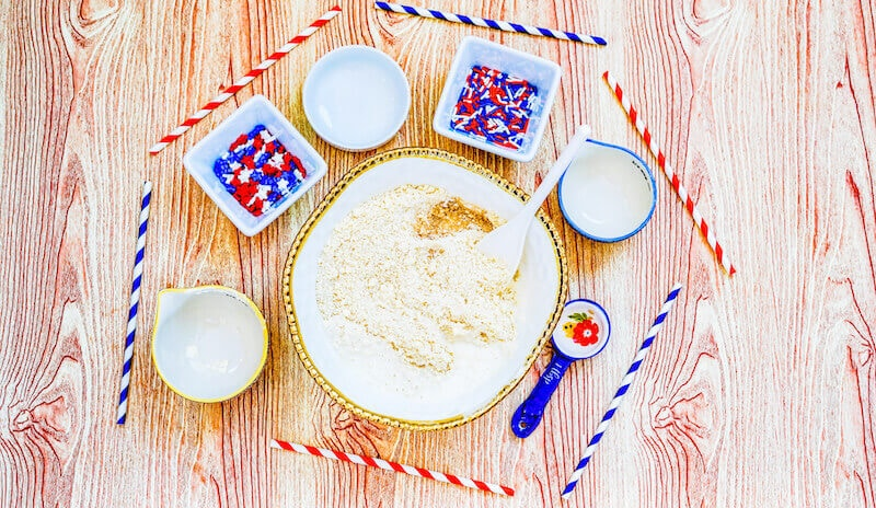 A bowl of butter and sugar mixed together next to two small bowls of milk and vanilla extract.