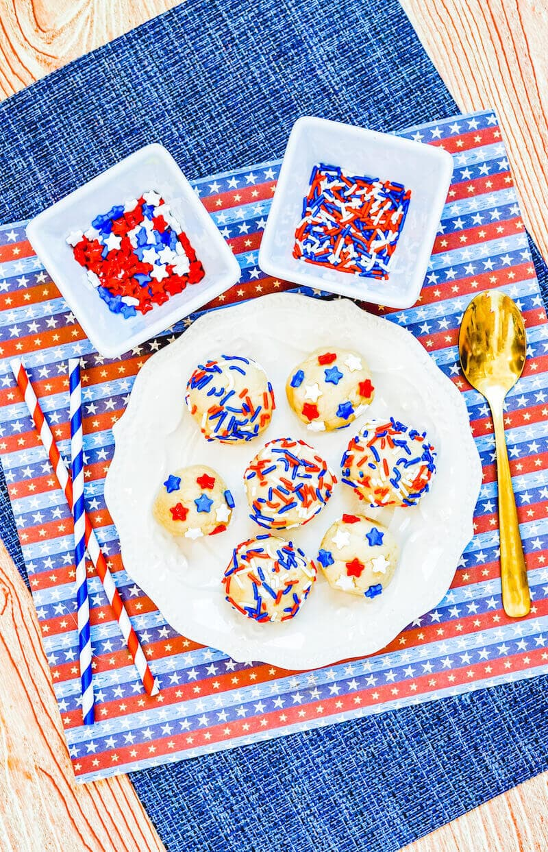 Overhead shot of edible sugar cookie dough rolled into balls on a white plate, next to a bold spoon and bowls of sprinkles.