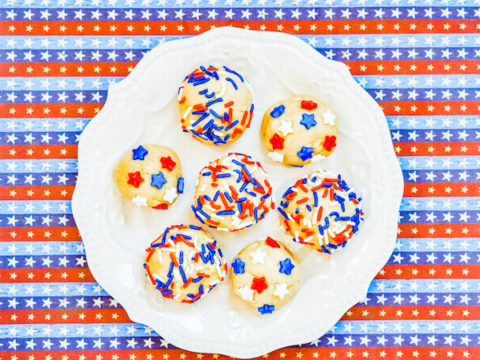 A plate of cookie dough in balls and topped with sprinkles.