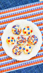 A red white and blue striped placemat topped with a white plate of edible sugar cookie dough.
