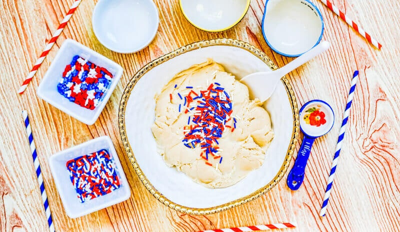 A bowl of sugar cookie dough topped with patriotic sprinkles.