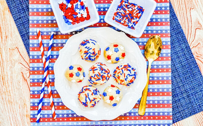 A white plate filled with balls of sugar cookie dough topped with patriotic sprinkles.