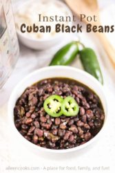 "A bowl of black beans topped with two slices of jalalpeno and the words ""instant pot cuban black beans"" in brown lettering."