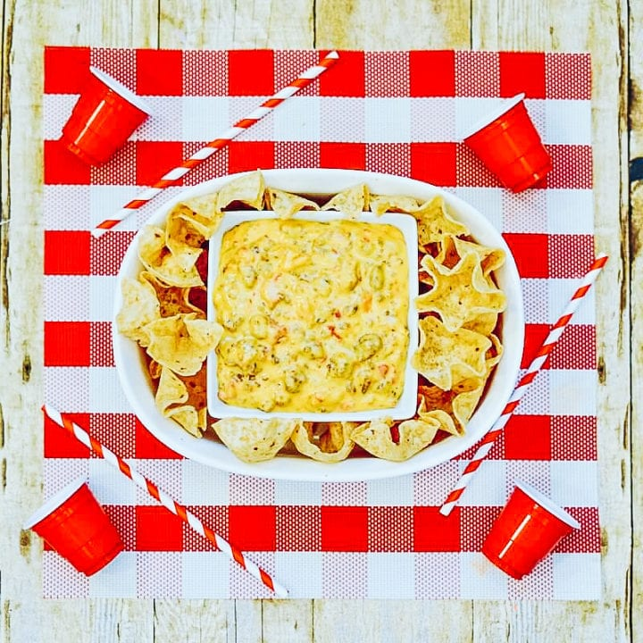 A red and white checkered placemat topped with a white oval serving dish filled with Rotel Dip and tortilla chips.