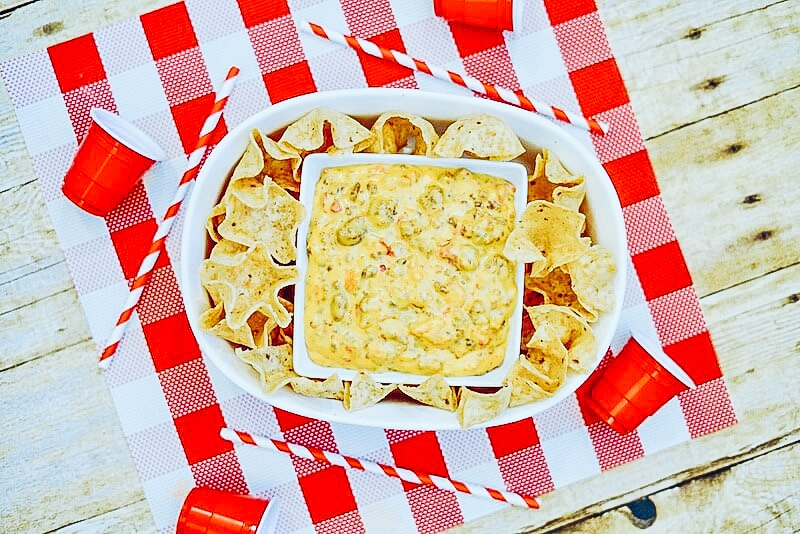 An oven serving dish with tortilla chips and Rotel Dip in the center, on top of a red and white checkered placemat.