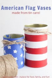 "Two tin cans painted to look like the American flag with the words ""American flag vases"" in blue letters."