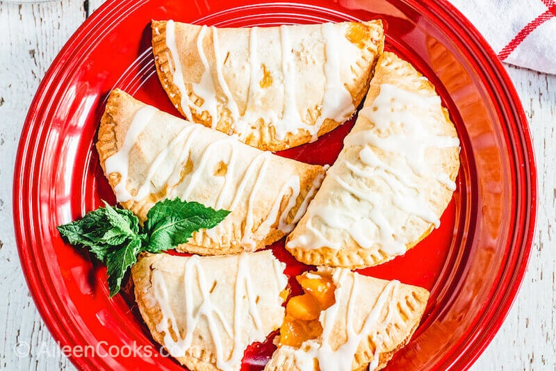 A red plate filled with 4 peach hand pies that are drizzled with icing.