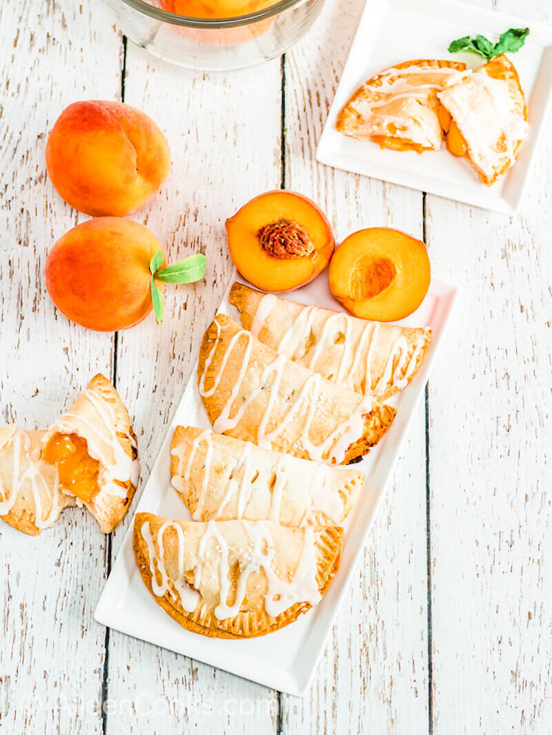 A white serving tray filled with peach hand pies and next to a peach cut in half.