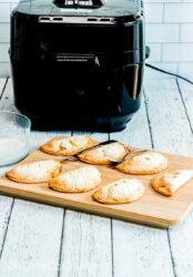 A wooden cutting board filled with hand pies, in front of a black air fryer.