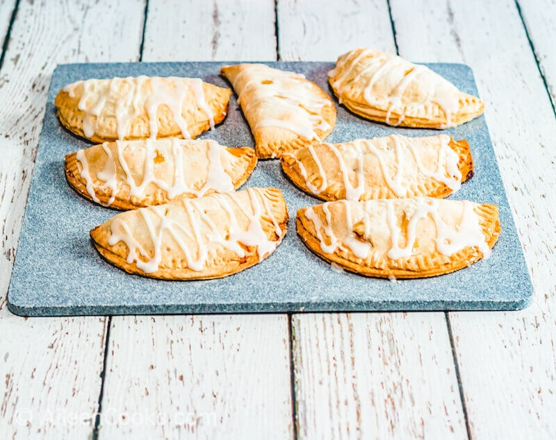 A cookie sheet filled with peach hand pies that are drizzled with icing.
