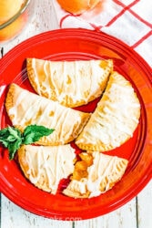 A red plate filled with peach hand pies.