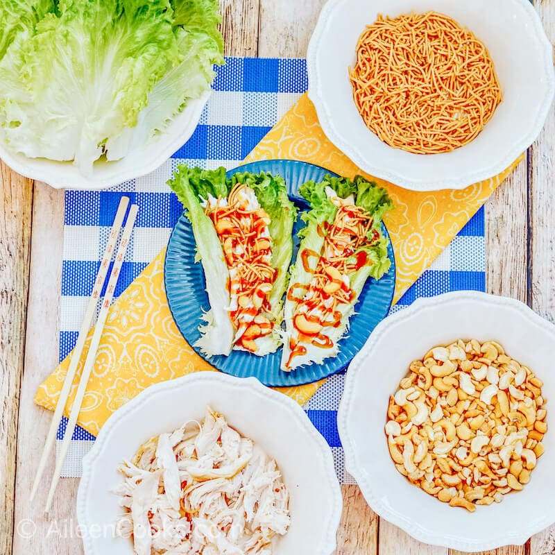A blue plate filled with two lettuce wraps and surrounded by ingredients to make asian chicken wraps.