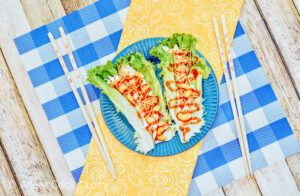 A blue plate of lettuce wraps on top of a yellow cloth.