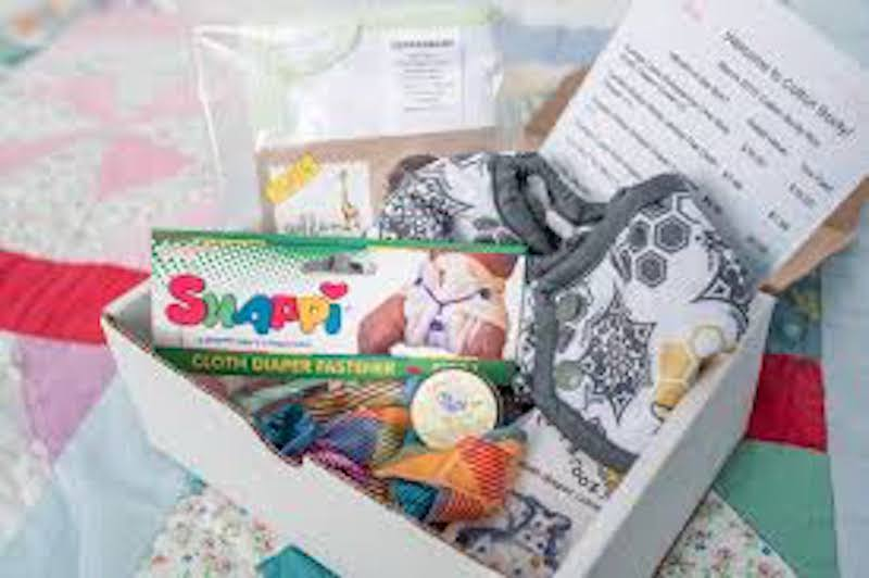The inside of the Cotton Booty subscription box, featuring cloth diapers and accessories for cloth diapers.