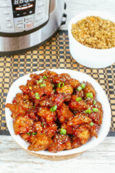 Overhead shot of a bowl of general tso's chicken and a bowl of brown rice.