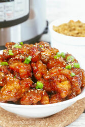 A bowl of general tso's chicken in front of a small bowl of brown rice and an instant pot.