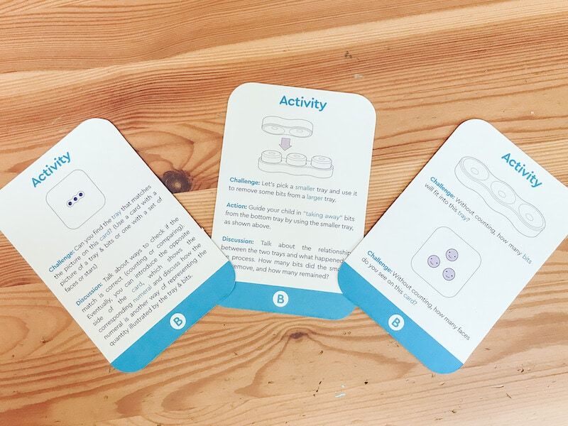 Three blue and white Kontu activity cards on a wooden table.