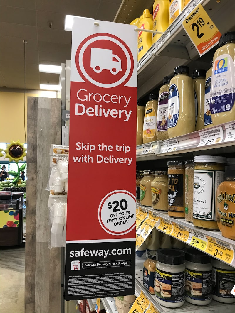 A long rectangular sign with the words Grocery Deliver and Safeway.com
