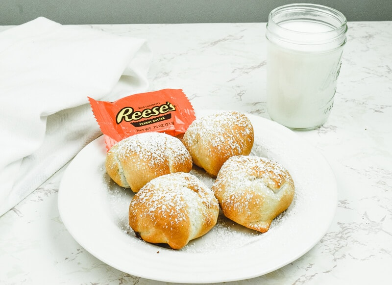 A white plate of four air fried Reeses next to a glass of milk.