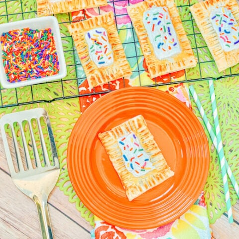 A cooling rack of pop tarts above an orange plate with a pop tart.