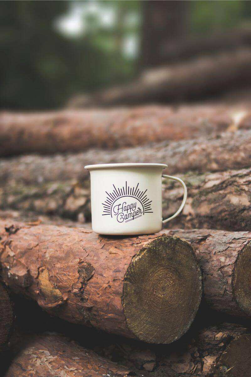 "A coffee mug that says ""happy camper"" on a log."