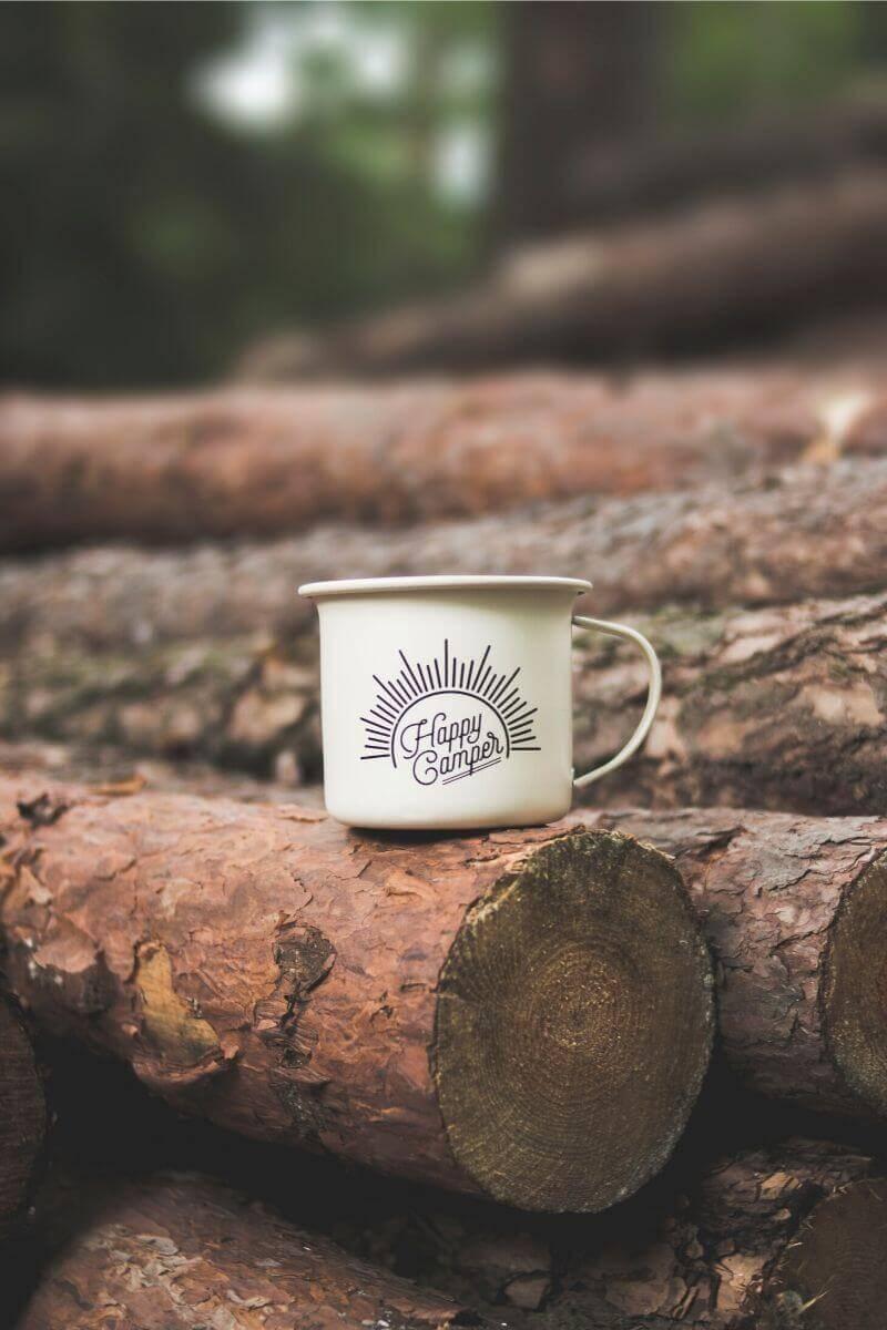 """A coffee mug that says """"happy camper"""" on a log."""