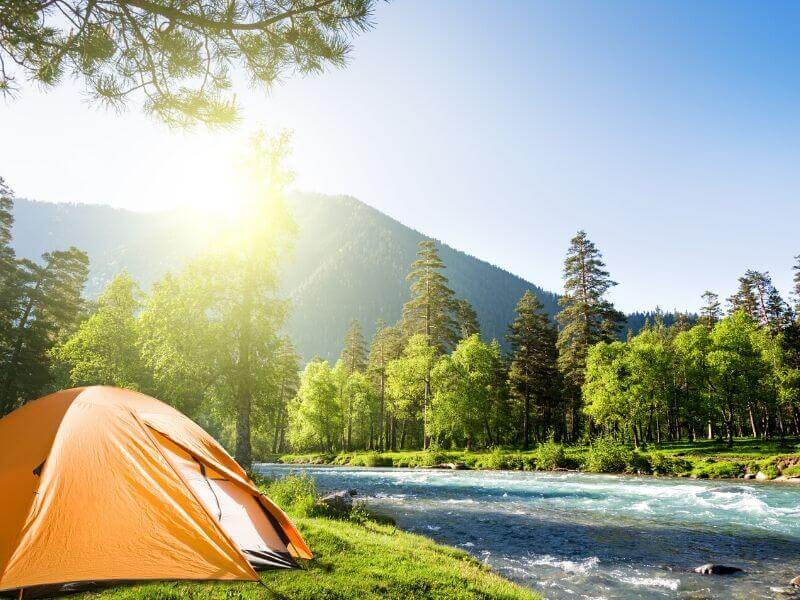 An orange tent next to a river with the sun shining.