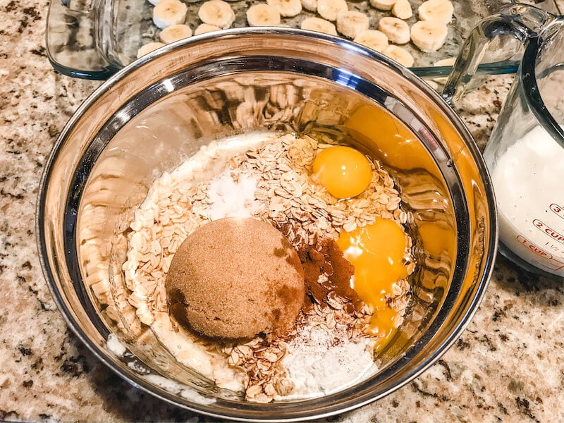 A metal mixing bowl with brown sugar, eggs, milk, and seasonings.