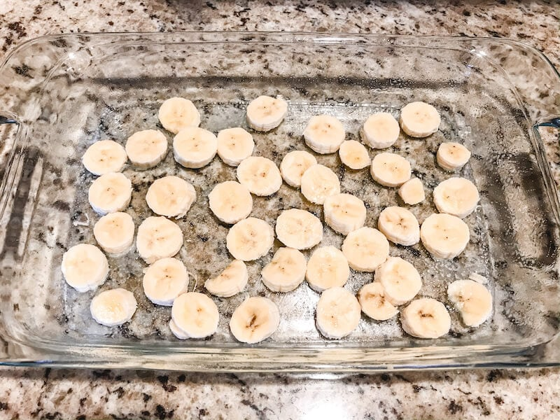 A glass baking dish with sliced banana arranged on the bottom.
