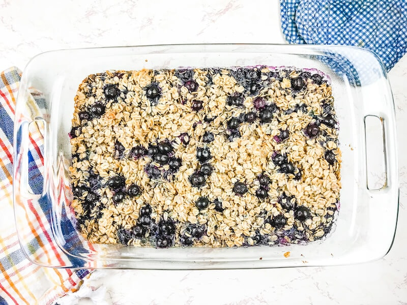 A glass baking dish filled with baked oatmeal and topped with blueberries.