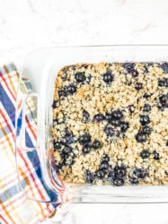 A glass dish of blueberry baked oatmeal next to a striped towel.