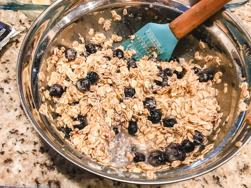 Baked oatmeal ingredients with blueberries mixed in.