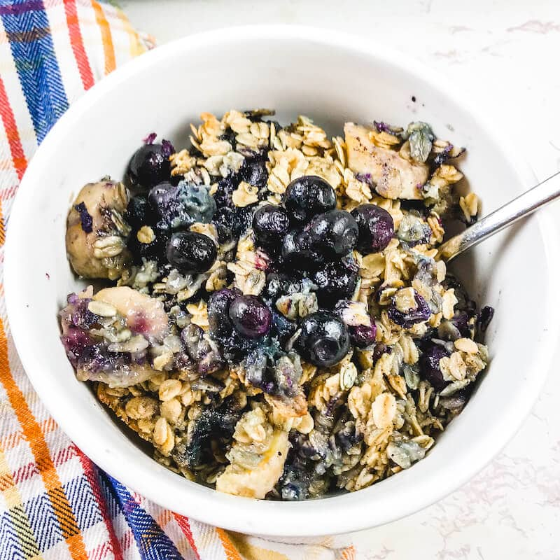 Close up of baked oatmeal with blueberries in a white bowl.