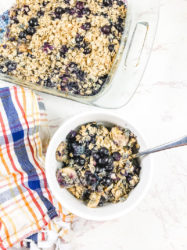 A white bowl of blueberry baked oatmeal below a baking dish of baked oatmeal.