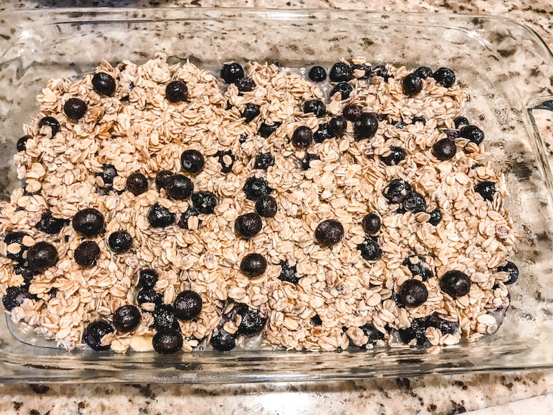 Blueberry baked oatmeal spread into a baking dish and ready to be cooked.