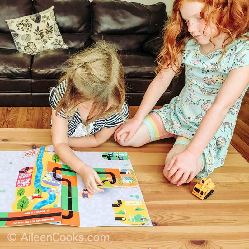 Two little girls working together to play a coding board game.