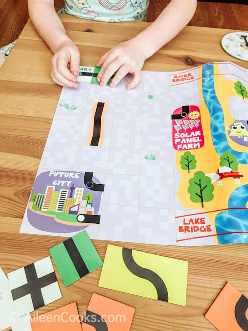 A child's hands setting up the track on a magnetic coding board game.