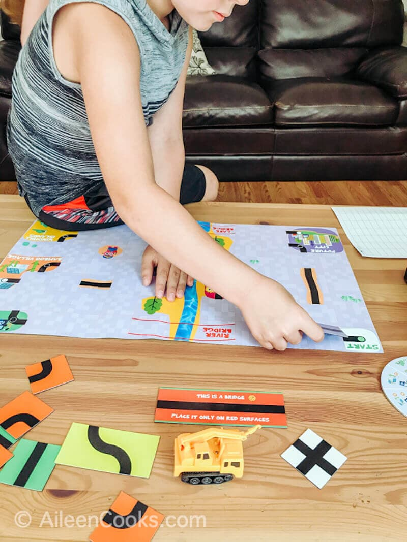A boy sitting on the end of a coffee table and building the track for his coding board game.