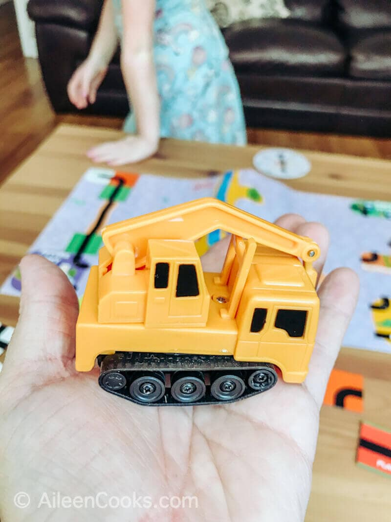 A hand holding up a toy construction truck.