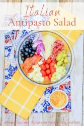 """A bowl of antipasto salad with the words """"Italian Antipasto salad"""" in orange lettering."""