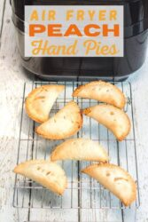 """A cooling rack of hand pies in front of an air fryer with the words """"air fryer peach hand pies"""" in orange lettering."""